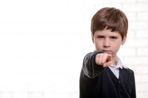 young boy pointing finger at camera
